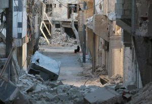 A woman sits amid damaged buildings in the rebel-held al-Myassar neighborhood of Aleppo, Syria. REUTERS/Abdalrhman Ismail